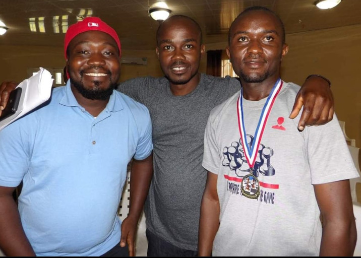 Past and current Liberian National Champions pose for a photo. From left, former Champions James Stephen Tondo III , red cap FM Barcon Harmon, in the middle and2019 Liberia National Champion Thomas Saah Current Champion with medal round his neck.