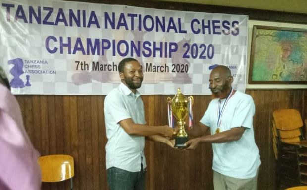 FM Hemed Mlawa (left) receives his trophy from Yusuf Mdoe. Photo credit Tanzania Chess Association.