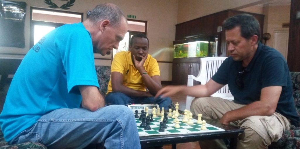 Roberto Villuela (left)of Nairobi Chess Club takes on Jordi Herms Agullo of Granollers Club D'Escacs at the Goan Gymkhana. Githinji Hinga of Mini Chess Kenya looks on. Photo credit Kim Bhari.