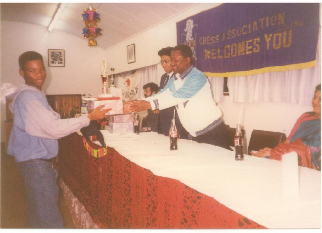 Aderito Pedro receives his prize for winning the 1993 Africa Junior Chess Championship from the late Chairman of Kenya Chess Association Fred Sagwe while Vice-Chairman Francis Rodrigues looks on. The event was held at the YMCA in Nairobi, Kenya and ran from 11th to 26th December 1993. Photo credit Kim Bhari.