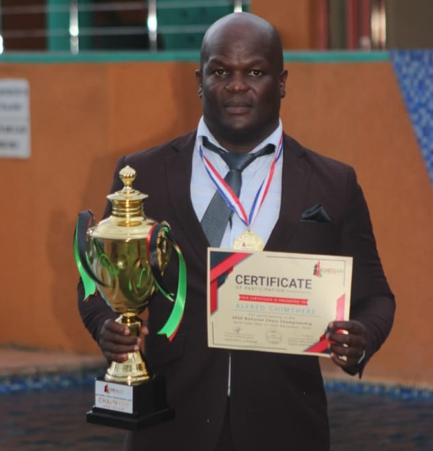 CM Alfred Chimthere posing with his trophy for winning the 2020 Malawi National Chess Championship.