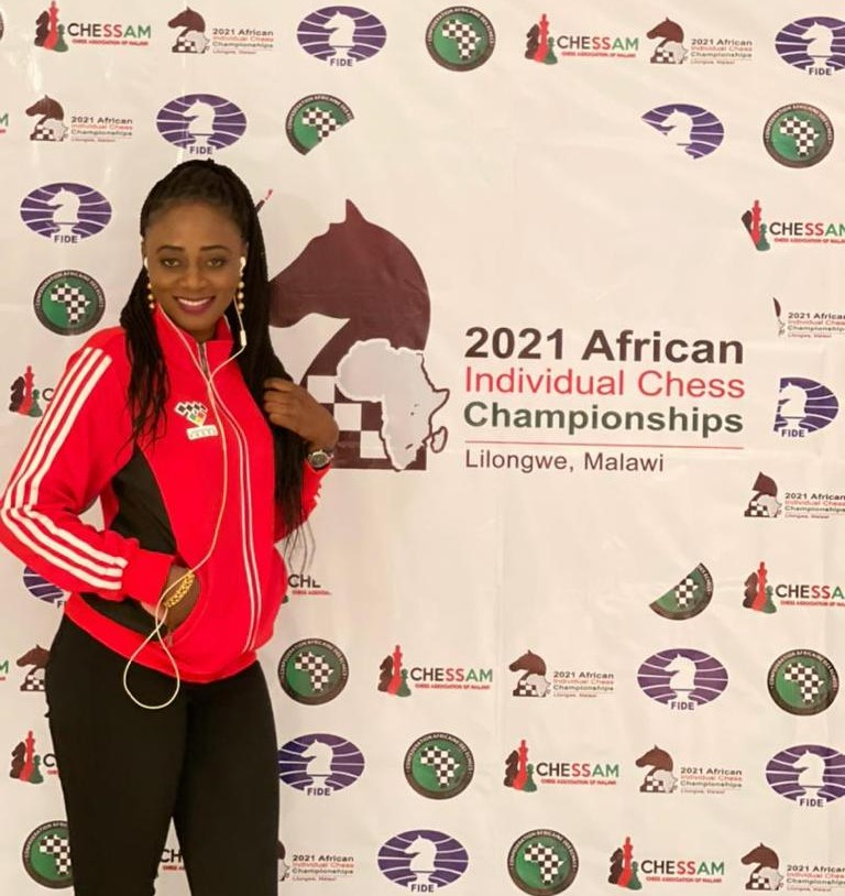The charming Khady Niang of Senegal poses in front of the poster for the 2021 African Individual Chess Championship.