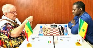 Bernard Lesbros (left) carefully checks his score sheet in his game against Sékou Aransbène Badji.