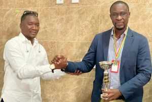Mbaye Abdoulaye Bamba representing the Ministry of Sports (left) presents the winner Amadou LamineCissé with his trophy.