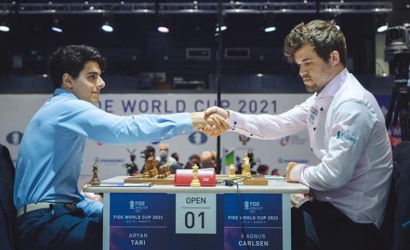 GM Aryan Tari (left) shakes hands with World Champion GM Magnus Carlsen.
