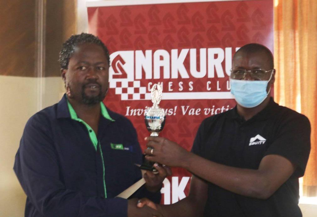 CM Ben Magana (left) receives his trophy from Chess Kenya President Benard Wanjala. Photo credit 64 Chess Squares.